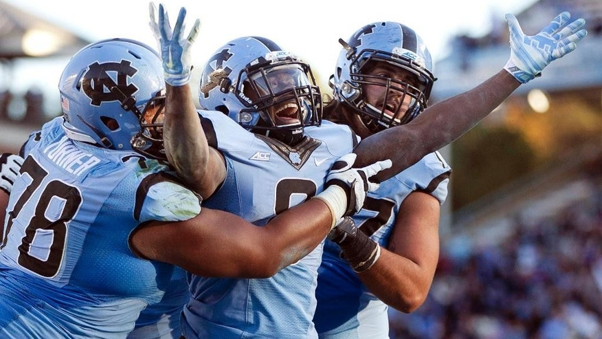 North Carolina's T.J. Logan, center, celebrates the game-winning touchdown after a one-yard run with teammates Landon Turner (78) and John Ferranto after an NCAA college football game against Pittsburgh, Saturday, Nov. 15, 2014, in Chapel Hill, N.C. North Carolina won 40-35. (AP Photo/The News & Observer, Robert Willett)