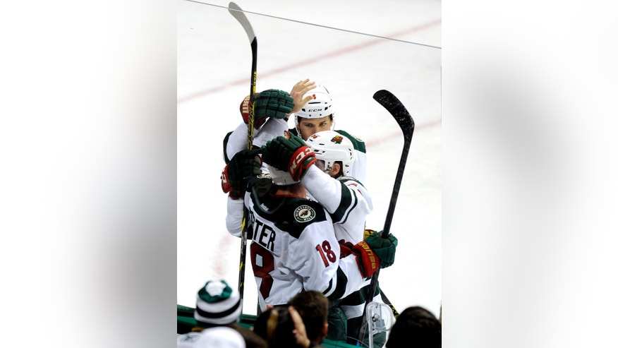Minnesota Wild center Ryan Carter (18), defenseman Stu Bickel (4) and left wing Erik Haula celebrate after Haula's goal in the second period during an NHL hockey game against the Dallas Stars, Saturday, Nov. 15, 2014, in Dallas. (AP Photo/Matt Strasen)