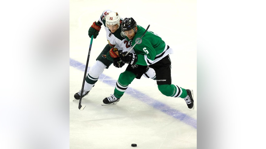 Minnesota Wild right wing Nino Niederreiter (22) and Dallas Stars defenseman Trevor Daley (6) go after the puck in the first period of an NHL hockey game, Saturday, Nov. 15, 2014, in Dallas. (AP Photo/Matt Strasen)