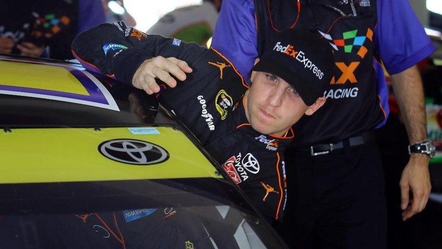 Driver Denny Hamlin climbs int his car as he prepares to practice for  Sunday's NASCAR Sprint Cup series auto race, Saturday, Nov. 15, 2014 in Homestead, Fla. (AP Photo/David Graham)