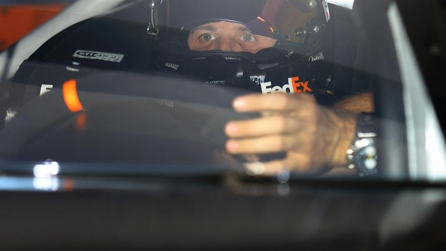 Joey Logano watches in the garage as he prepares to practice for  Sunday's NASCAR Sprint Cup sereis auto race, Saturday, Nov. 15, 2014 in Homestead, Fla. (AP Photo/David Graham)
