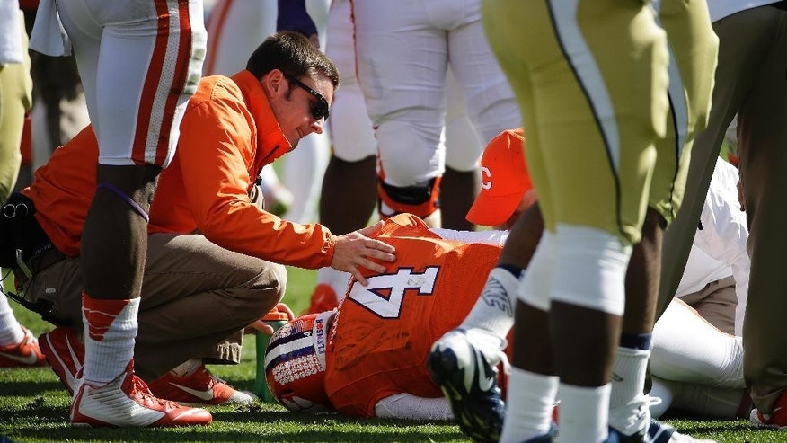 A trainer tends to Clemson quarterback Deshaun Watson after he went down with an injury in the first quarter of an NCAA college football game against Georgia Tech, Saturday, Nov. 15, 2014, in Atlanta. (AP Photo/David Goldman)