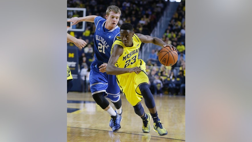 Michigan guard Caris LeVert (23) drives on Hillsdale forward Lucas Grose (21) during the first half of an NCAA college basketball game in Ann Arbor, Mich., Saturday, Nov. 15, 2014. (AP Photo/Carlos Osorio)