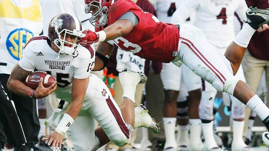 Alabama linebacker Trey DePriest (33) is fouled after a face mask grab against Mississippi State quarterback Dak Prescott (15) during the first half of an NCAA college football game Saturday, Nov. 15, 2014, in Tuscaloosa, Ala. (AP Photo/Brynn Anderson)