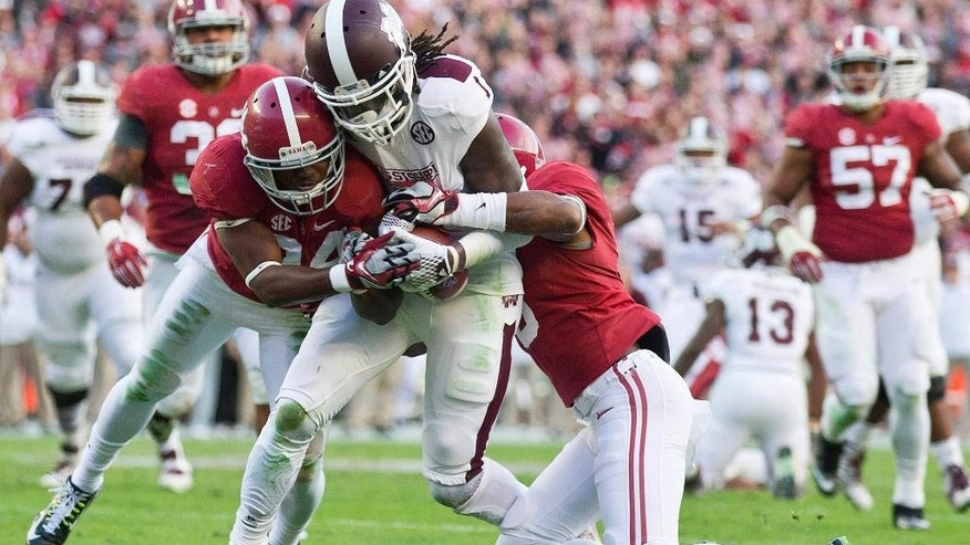 Mississippi State wide receiver De'Runnya Wilson (1) is tackled by Alabama defensive back Cyrus Jones, right, and Alabama defensive back Geno Smith (24) during the first half of an NCAA college football game Saturday, Nov. 15, 2014, in Tuscaloosa, Ala. (AP Photo/Brynn Anderson)