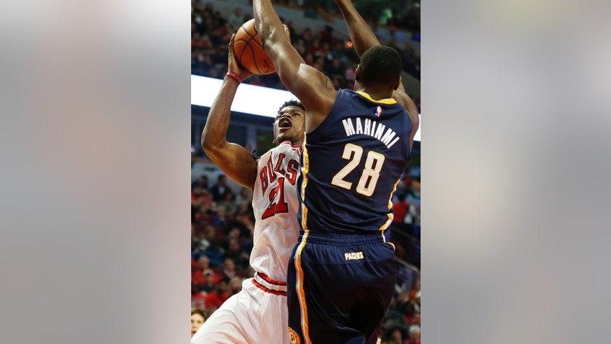 Chicago Bulls guard Jimmy Butler (21) shoots past Indiana Pacers' Ian Mahinmi (28) during the first half of an NBA basketball game on Saturday, Nov. 15, 2014, in Chicago. (AP Photo/Andrew A. Nelles)