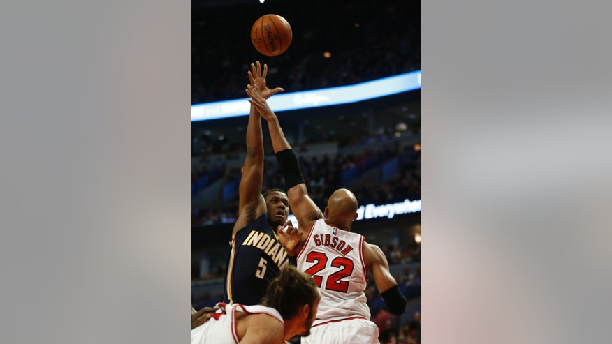 Indiana Pacers' Lavoy Allen (5) shoots past Chicago Bulls forward Taj Gibson (22) during the first half of an NBA basketball game on Saturday, Nov. 15, 2014, in Chicago. (AP Photo/Andrew A. Nelles)