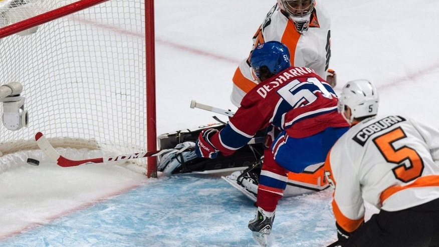 Montreal Canadiens' David Desharnais scores past Philadelphia Flyers goalie Ray Emery as defenseman Braydon Coburn looks on during the first period of their NHL hockey game in Montreal on Saturday, Nov. 15, 2014. (AP Photo/The Canadian Press, Paul Chiasson)