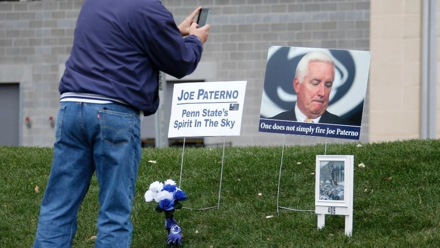 A Penn State football fan takes a picture of items left at the site outside Beaver Stadium where once stood a statue of former Penn State football coach Joe Paterno before an NCAA college football game between the Penn State and the Temple in State College, Pa., Saturday, Nov. 15, 2014. (AP Photo/Gene J. Puskar)