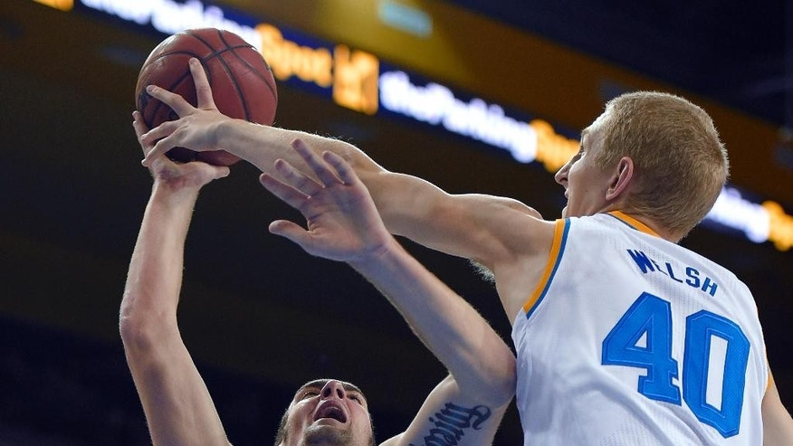 UCLA center Thomas Welsh, right, blocks the shot of Montana State forward Danny Robison during the first half of an NCAA college basketball game, Friday, Nov. 14, 2014, in Los Angeles. (AP Photo/Mark J. Terrill)