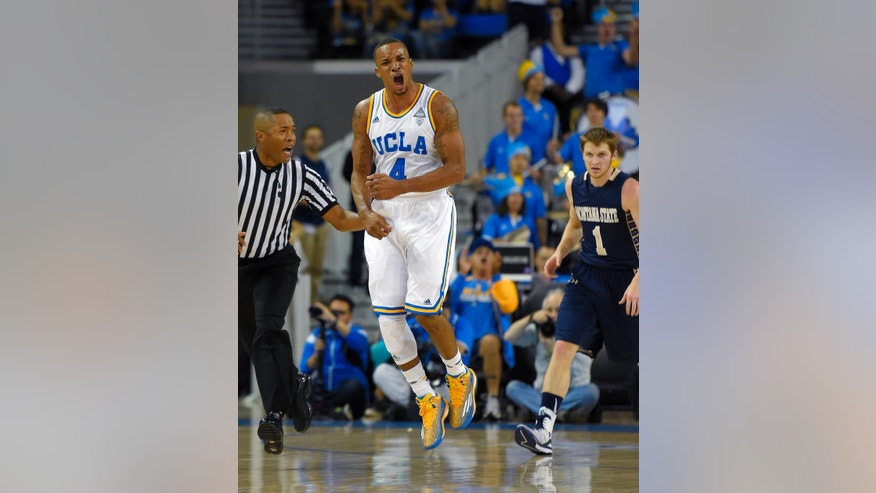 UCLA guard Norman Powell, center, celebrates after scoring as Montana State guard Stephan Holm, right, watches during the first half of an NCAA college basketball game, Friday, Nov. 14, 2014, in Los Angeles. (AP Photo/Mark J. Terrill)
