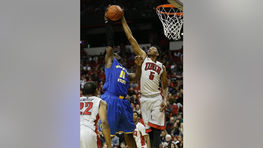 UNLV forward Christian Wood blocks a shot by Morehead forward Marcus Fuggins during the first half of an NCAA college basketball game Friday, Nov. 14, 2014, in Las Vegas. (AP Photo/John Locher)