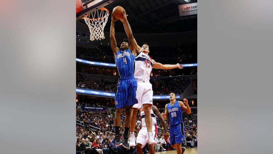 Orlando Magic guard Elfrid Payton (4) has his shot blocked by Washington Wizards forward Kris Humphries (43) in the first half of an NBA basketball game, Saturday, Nov. 15, 2014, in Washington. (AP Photo/Alex Brandon)