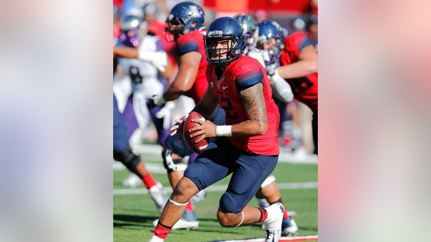 Arizona quarterback Anu Solomon (12) runs for a first down against Washington during the first half of an NCAA college football game, Saturday, Nov. 15, 2014, in Tucson, Ariz. (AP Photo/Rick Scuteri)