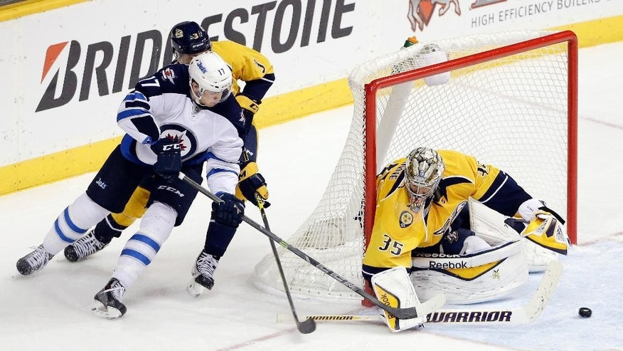 Nashville Predators goalie Pekka Rinne (35), of Finland, blocks a shot by Winnipeg Jets left wing Adam Lowry (17) in the third period of an NHL hockey game Saturday, Nov. 15, 2014, in Nashville, Tenn. The Predators won 2-1. (AP Photo/Mark Humphrey)
