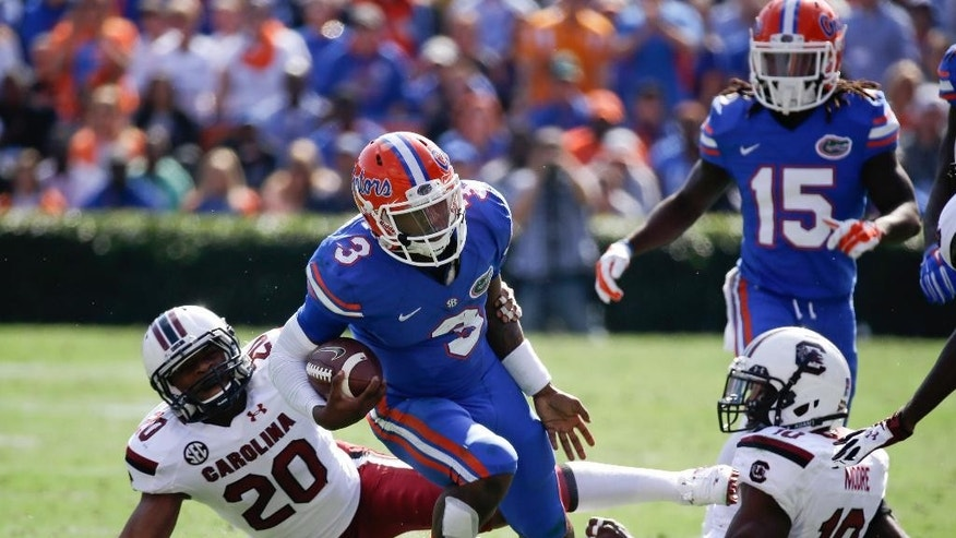 Florida quarterback Treon Harris (3) runs for yardage between South Carolina safety T.J. Gurley (20) and linebacker Skai Moore (10) during the first half of an NCAA college football game in Gainesville, Fla., Saturday, Nov. 15, 2014. (AP Photo/John Raoux)