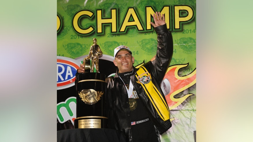In this photo submitted by the NHRA, Tony Schumacher celebrates his NHRA Top Fuel title following qualifying at the Auto Club NHRA Finals drag races Saturday, Nov. 15, 2014, in Pomona, Calif. This is Schumacher's eighth career championship and first since 2009. (AP Photo/NHRA, Marc Gewertz)