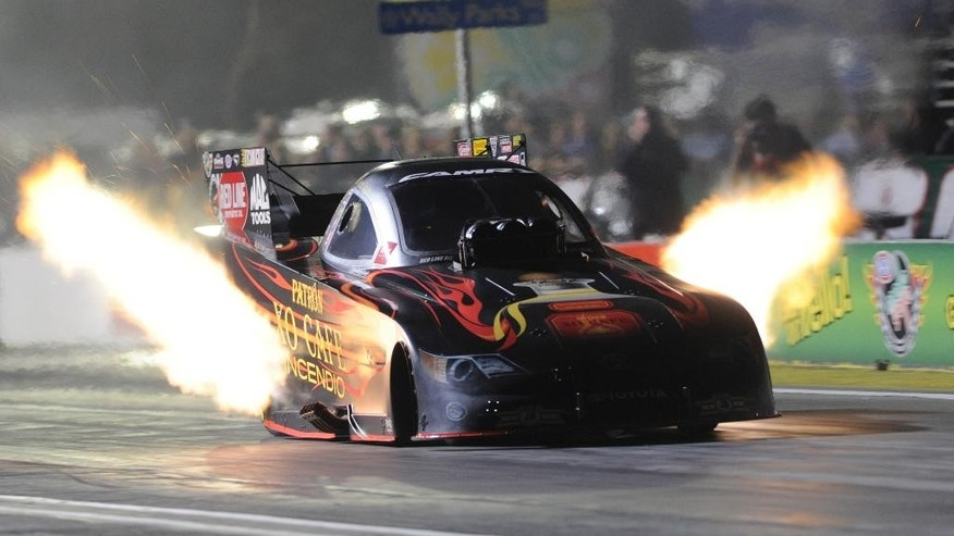 In this photo provided by the NHRA, Alexis DeJoria makes a run in Funny Car qualifying at the Auto Club NHRA Finals drag races, Saturday, Nov. 15, 2014, in Pomona, Calif. DeJoria took the No. 1 qualifying spot. Jerry (AP Photo/NHRA, Jerry Foss)
