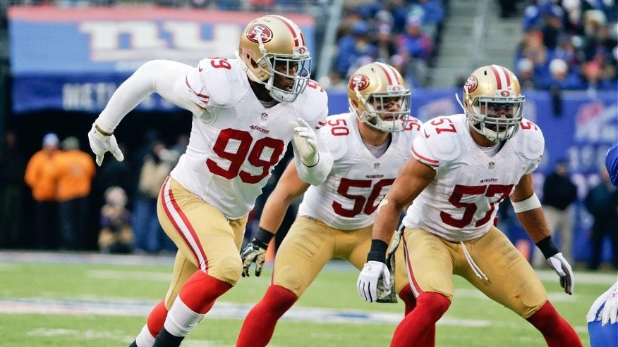 San Francisco 49ers outside linebacker Aldon Smith (99) blitzes as teammates Michael Wilhoite (57) and Chris Borland (50) look on during the first half of an NFL football game against the New York Giants, Sunday, Nov. 16, 2014, in East Rutherford, N.J. (AP Photo/Julio Cortez)