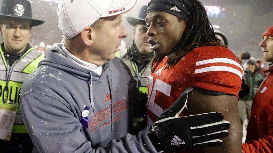 Wisconsin's Melvin Gordon talks to Nebraska head coach Bo Pelini after Wisconsin won 59-24 in an NCAA college football game Saturday, Nov. 15, 2014, in Madison, Wis.  Gordon rushed for a major college-record 408 yards and four touchdowns in the game. (AP Photo/Morry Gash)