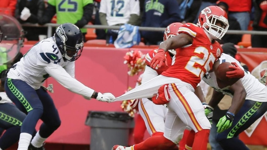 Kansas City Chiefs running back Jamaal Charles (25) scores a touchdown as Seattle Seahawks cornerback Byron Maxwell (41) pulls on his jersey  in the first half of an NFL football game in Kansas City, Mo., Sunday, Nov. 16, 2014. (AP Photo/Charlie Neibergall)