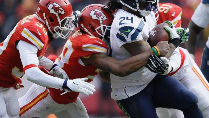 Seattle Seahawks running back Marshawn Lynch (24) is tackled by Kansas City Chiefs free safety Husain Abdullah, left, outside linebacker Tamba Hali (91), and strong safety Eric Berry, second left, in the first half of an NFL football game in Kansas City, Mo., Sunday, Nov. 16, 2014. (AP Photo/Charlie Neibergall)