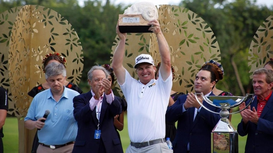Charley Hoffman holds up his trophy after winning the OHL Classic at Mayacoba golf tournament in Playa del Carmen, Mexico, Sunday, Nov. 16, 2014. Hoffman rallied from a three-shot deficit Sunday by closing with a 5-under 66 for a one-shot victory over Shawn Stefani. (AP Photo/Israel Leal)
