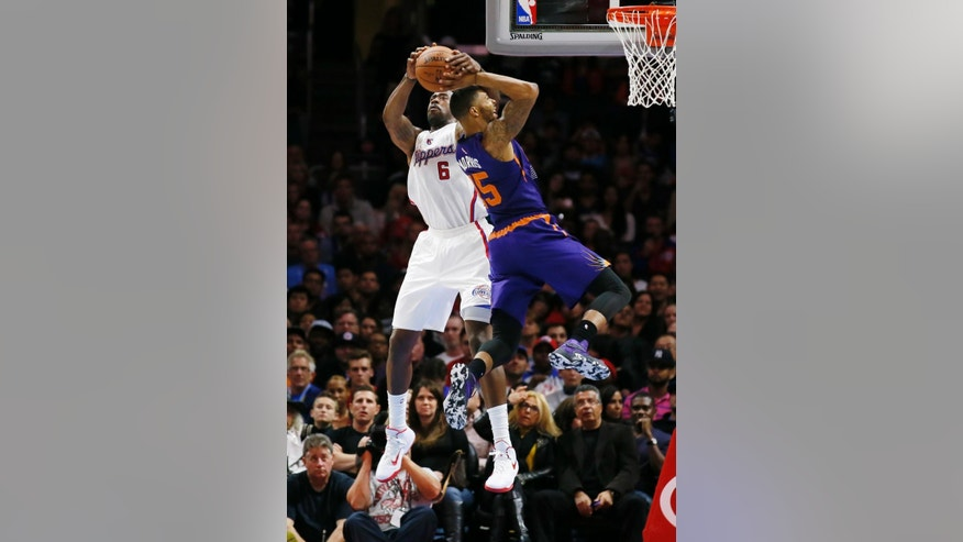 Los Angeles Clippers' DeAndre Jordan, left, grabs the ball away from Phoenix Suns' Marcus Morris, right, as he goes to the hoop while a jump ball is called during the first half of an NBA basketball game Saturday, Nov. 15, 2014, in Los Angeles. (AP Photo/Danny Moloshok)