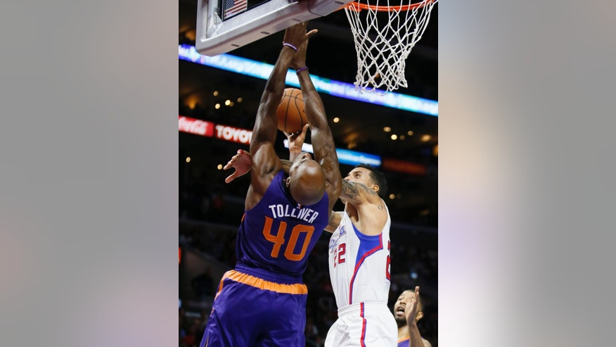Los Angeles Clippers' Matt Barnes, right, shoots the ball and collides with Phoenix Suns' Anthony Tucker, left, causing his mouth to bleed, during the first half of an NBA basketball game Saturday, Nov. 15, 2014, in Los Angeles. (AP Photo/Danny Moloshok)