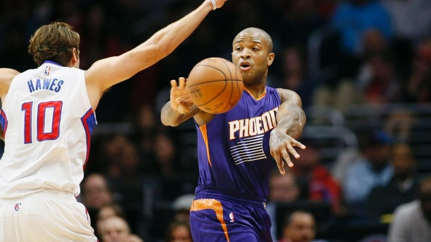 Phoenix Suns' P.J. Tucker, right, passes the ball around Los Angeles Clippers' Spencer Hawes, left, during the first half of an NBA basketball game Saturday, Nov. 15, 2014, in Los Angeles. (AP Photo/Danny Moloshok)
