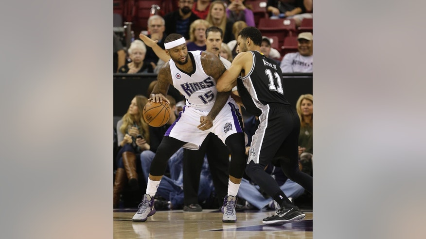 San Antonio Spurs center Jeff Ayres, right, tries to stop the drive of Sacramento Kings center DeMarcus Cousins during the first quarter of an NBA basketball game in Sacramento, Calif., Saturday, Nov. 15, 2014.(AP Photo/Rich Pedroncelli)