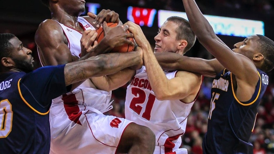 Wisconsin's Nigel Hayes, second from left, and Josh Gasser (21) pull a defensive rebound away from Chattanooga's Duke Ethridge, left, and Eric Robertson during the first half of an NCAA college basketball game Sunday, Nov. 16, 2014, in Madison, Wis. (AP Photo/Andy Manis)