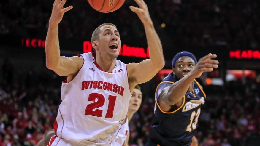 Wisconsin's Josh Gasser (21) gets a tipped ball away from Chattanooga's Tre' McLean during the first half of an NCAA college basketball game Sunday, Nov. 16, 2014, in Madison, Wis. (AP Photo/Andy Manis)