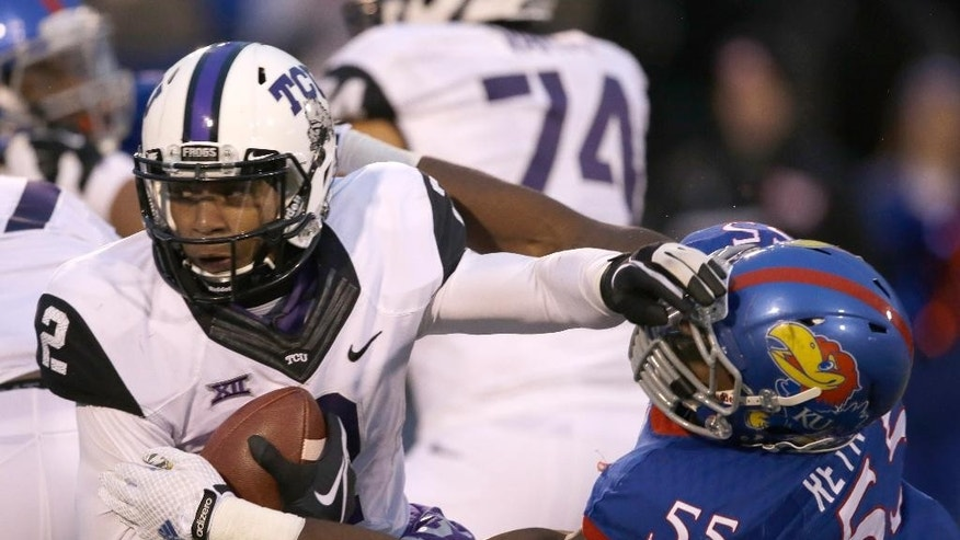 TCU quarterback Trevone Boykin (2) avoids a tackle by Kansas linebacker Michael Reynolds (55) during the second half of an NCAA college football game in Lawrence, Kan., Saturday, Nov. 15, 2014. TCU defeated Kansas 34-30. (AP Photo/Orlin Wagner)