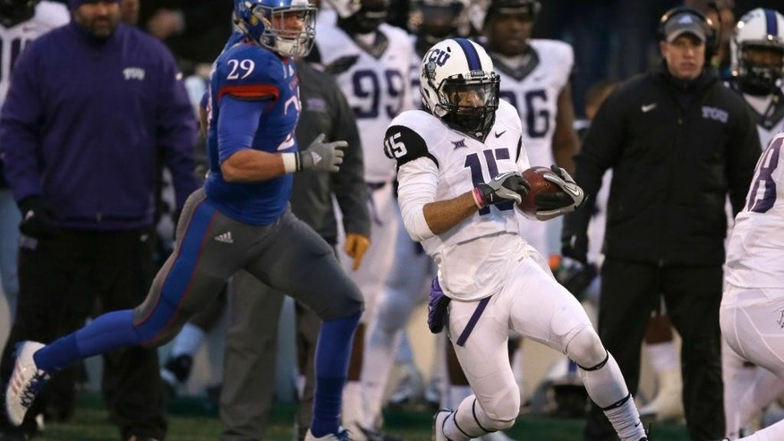 TCU punt returner Cameron Echols-Luper (15) cuts behind blockers and ahead of Kansas special teams player Joe Dineen Jr. (29) on his way for a touchdown during the second half of an NCAA college football game in Lawrence, Kan., Saturday, Nov. 15, 2014. TCU defeated Kansas 34-30. (AP Photo/Orlin Wagner)