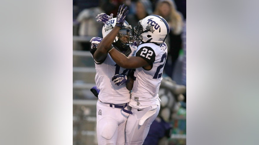 TCU running back Aaron Green (22) celebrates his touchdown with wide receiver David Porter, left, during the second half of an NCAA college football game against Kansas in Lawrence, Kan., Saturday, Nov. 15, 2014. TCU defeated Kansas 34-30. (AP Photo/Orlin Wagner)
