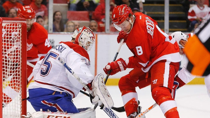 Montreal Canadiens goalie Dustin Tokarski (35) stops a Detroit Red Wings left wing Justin Abdelkader (8) shot in the first period of an NHL hockey game in Detroit, Sunday, Nov. 16, 2014. (AP Photo/Paul Sancya)
