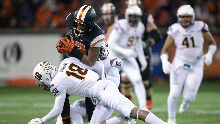 Oregon State receiver Jordan Villain (13) is tackled by Arizona State defenders James Johnson (18) and Lloyd Carrington during the second quarter of an NCAA college football game in Corvallis, Ore., Saturday, Nov. 15, 2014. (AP Photo/Troy Wayrynen)