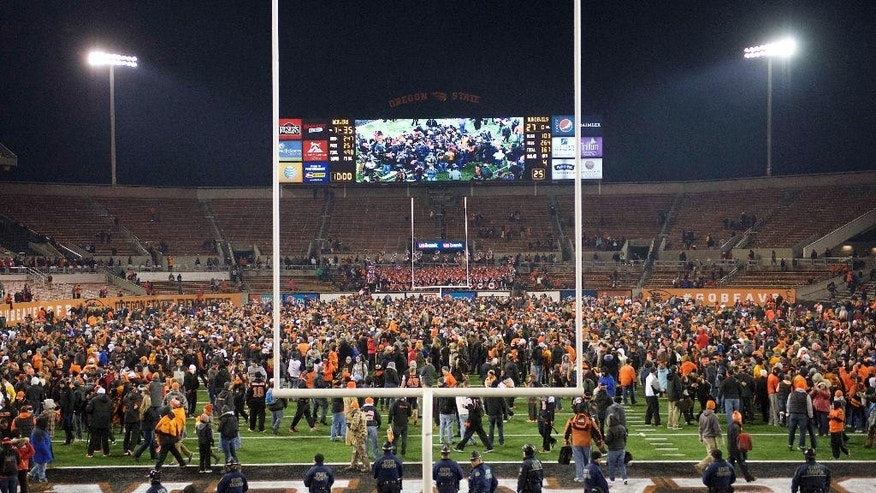 Oregon State football fans rush the field at the end of an NCAA college football game against Arizona State in Corvallis, Or., Saturday, Nov. 15, 2014. The Beavers beat the Sun Devils 35-27. (AP Photo/Troy Wayrynen)