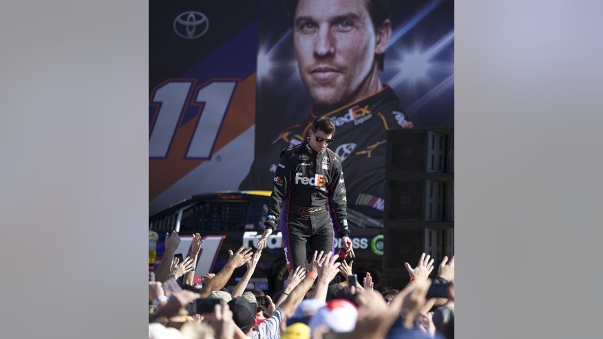 Denny Hamlin greets race fans before the NASCAR Sprint Cup championship series auto race, Sunday, Nov. 16,2014 in Homestead, Fla. (AP Photo/J Pat Carter)