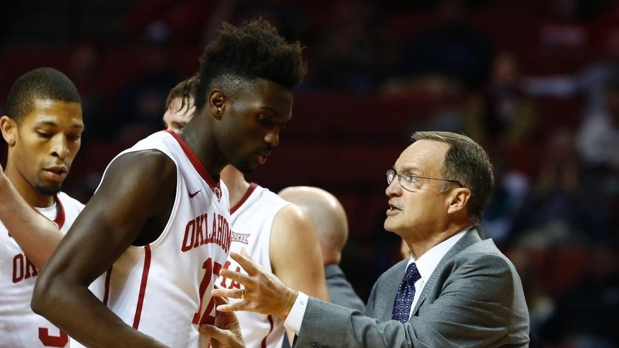 Oklahoma forward Khadeem Lattin (12) listens to head coach Lon Kruger during the first half of an NCAA college basketball game against Southeastern Louisiana in Norman, Okla., Sunday, Nov. 16, 2014. (AP Photo/ Alonzo Adams)