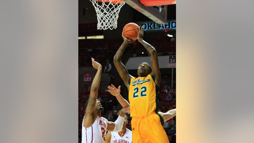 Southeastern Louisiana center Devonte Upson (22) goes up for a basket in front of Oklahoma forward TaShawn Thomas (35) during the first half of an NCAA college basketball game in Norman, Okla., Sunday, Nov. 16, 2014. (AP Photo/ Alonzo Adams)