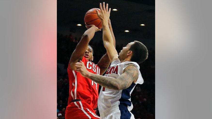 Cal State Northridge guard Aaron Parks (14) shoots over Arizona guard Gabe York (1) during the first half of an NCAA college basketball game, Sunday, Nov. 16, 2014, in Tucson, Ariz. (AP Photo/Rick Scuteri)