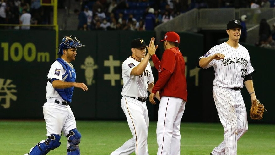 MLB All-Stars catcher Drew Butera, left, Mark Melancon, second from left, and Justin Morneau (33) celebrate with teammates after beating Japan 6-1 in Game 4 of their exhibition baseball series at Tokyo Dome in Tokyo, Sunday, Nov. 16, 2014. (AP Photo/Toru Takahashi)
