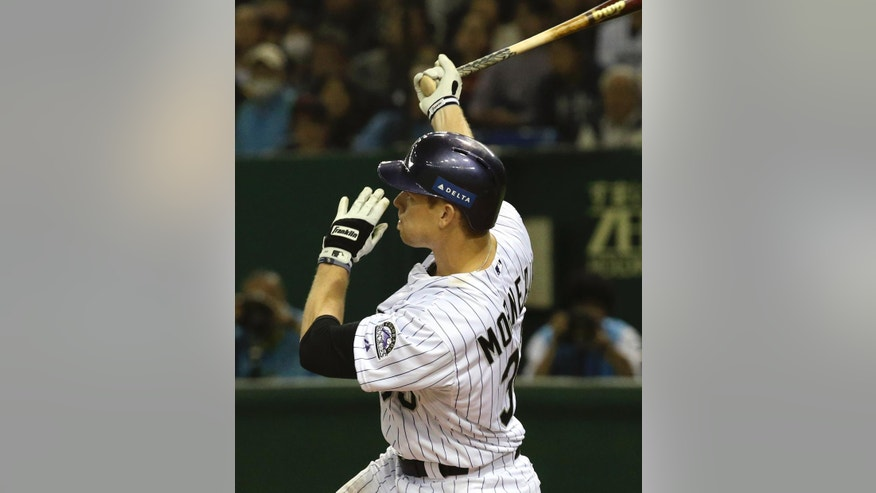 MLB All-Stars' Justin Morneau hits a three-run home run off Japan's starter Shintaro Fujinami in the third inning of Game 4 of their exhibition baseball series at Tokyo Dome in Tokyo, Sunday, Nov. 16, 2014. (AP Photo/Toru Takahashi)