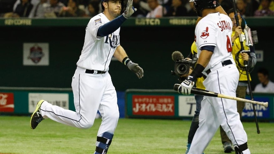 MLB All-Stars' Evan Longoria, left, celebrates with teammate Carlos Santana at home after hitting a solo shot off Japan's Minoru Iwata in the sixth inning of Game 4 of their exhibition baseball series at Tokyo Dome in Tokyo, Sunday, Nov. 16, 2014. (AP Photo/Toru Takahashi)