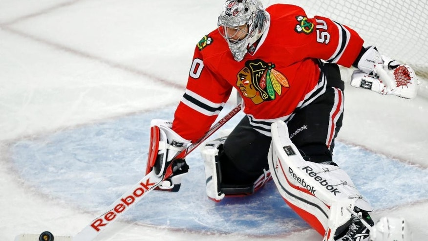 Chicago Blackhawks goalie Corey Crawford (50) deflects a Dallas Stars shot during the third period of an NHL hockey game on Sunday, Nov. 16, 2014, in Chicago. The Chicago Blackhawks won 6-2. (AP Photo/Andrew A. Nelles)