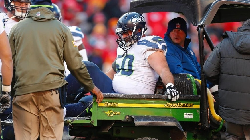 Seattle Seahawks center Max Unger (60) is taken off the field following an injury in the second half of an NFL football game against the Kansas City Chiefs in Kansas City, Mo., Sunday, Nov. 16, 2014. (AP Photo/Ed Zurga)