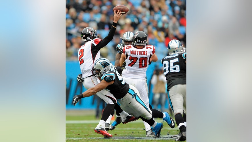 Atlanta Falcons' Matt Ryan (2) is hit by Carolina Panthers' Dwan Edwards (92) as he throws a pass in the first half of an NFL football game in Charlotte, N.C., Sunday, Nov. 16, 2014. (AP Photo/Mike McCarn)