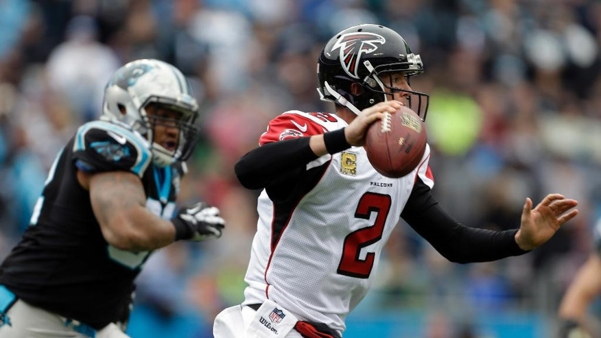 Atlanta Falcons' Matt Ryan (2) scrambles past Carolina Panthers' Dwan Edwards (92) in the first half of an NFL football game in Charlotte, N.C., Sunday, Nov. 16, 2014. (AP Photo/Bob Leverone)